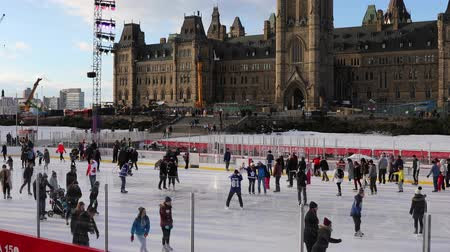 janeiro : Ottawa, Ontario, Canada - January 20th, 2018: People Ice Skating on Parliament Hill with Flag closeup at the end