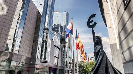 Waving flags and statue in front of European Union Parliament, Brussels