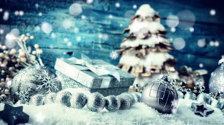 Christmas holiday setting with festive decorations in silver tone laying in snow. Christmas background, slider (dolly) shot, 4k