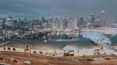 Сидней : Day To Night Cityscape Time Lapse Of Darling Harbour Skyline Sydney, NSW, Australia. Showing Busy Nightlife Traffic Including CBD, Bridge, Boats & People Walking Around Marina And Jetties