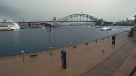 Ópera de sidney : Sydney Harbour Bridge Time Lapse & Skyline Cloudscape Shot From Sydney Opera House With People Walking At Circular Quay Wharf Harbour With Water Taxi Boats & Ferry Boat Traffic Around The Rocks Area