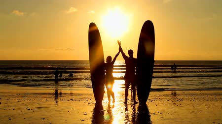 surf : Surfer couple in silhouette holding long surf boards at sunset on tropical beach
