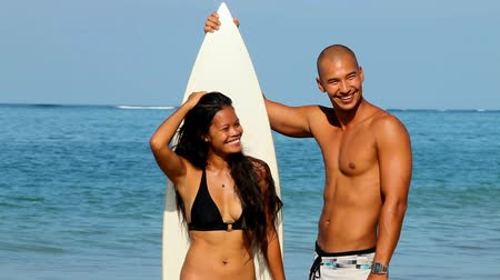 surfovat : Young Asian couple with surfboard on beach