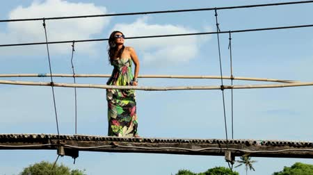 brown dress : Young beautiful asian woman standing on suspension bridge with long colourful dress