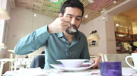 zupa : Handsome young man eating in soup a restaurant