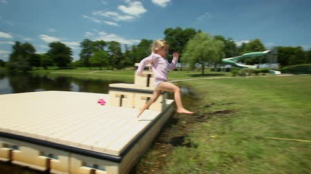 holding onto : Kid jumping onto grass near lake in France Stock Footage