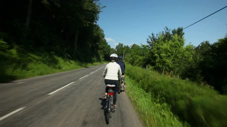 cycle : Slow motion - Retired couple cycling on road in village in France