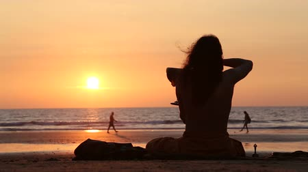 goa beach : GOA, INDIA - 21 JANUARY 2015: Man sitting on beach at sunset playing music to the sun. Stock Footage