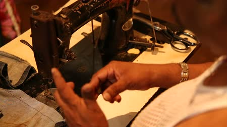 local : Indian man sewing at market workshop in Goa.