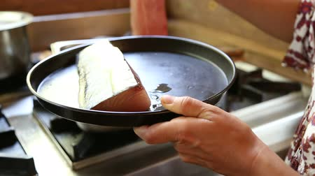 pans : Woman putting fish in pan.