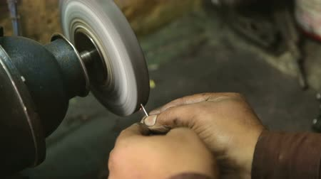 минимальный : Close view of man sharpening needle of sewing machine.