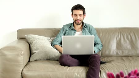 в чате : Young adult man sitting on couch in living room and having video chat Стоковые видеозаписи