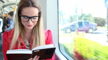 livro : Cute blond woman reading book while driving in tram