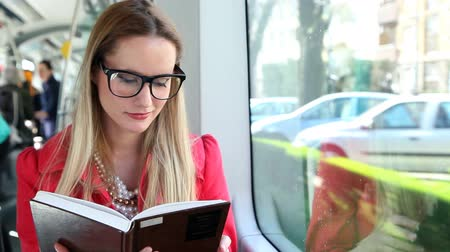 enciclopédia : Beautiful blond woman smiling while reading book and driving in tram