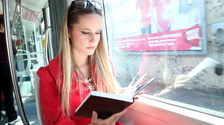 enciclopédia : Beautiful blond woman riding tram, reading book on sunny day