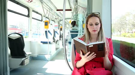 enciclopédia : Beautiful woman riding tram, while reading book