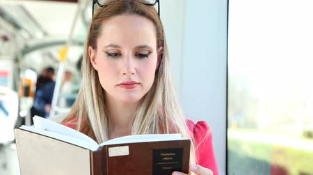 livro : Beautiful young adult woman sitting and reading in tram