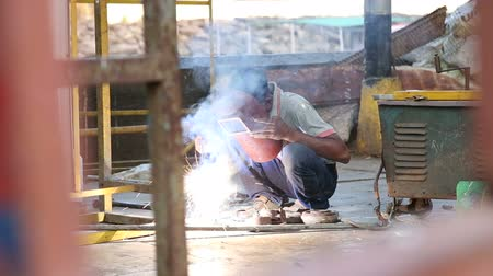 spawanie : MUMBAI, INDIA - 10 JANUARY 2015: Worker with a protective mask welding in a workshop in Mumbai.
