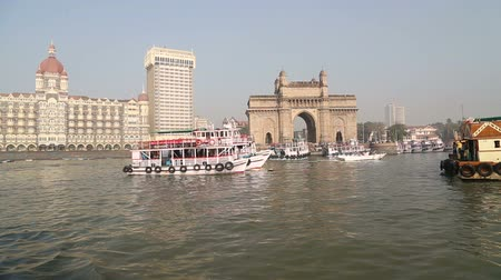bina : Boats floating on water in bay in Mumbai, with building in background. Stok Video