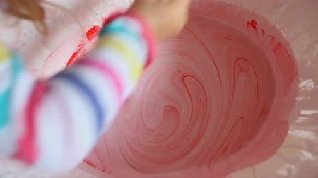 смешивание : Mixing red paint in bucket of white paint