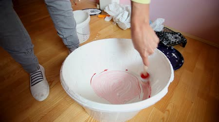 full bucket : Mixing red paint in bucket of white paint