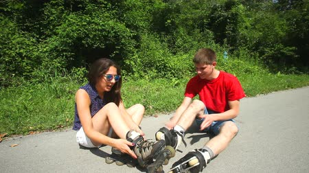 roller blading : Young woman and man sitting on track, putting their inline-skate  on their feet. Stock Footage