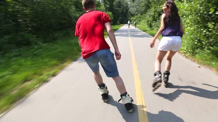 roller blading : Young woman and man rollerblading on a beautiful sunny summer day in park, holding hands Stock Footage