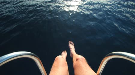 serene : Man sitting at the bow of the boat with feet and legs overboard