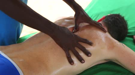 вера : Sri Lankan man giving shoulder oil massage to Caucasian man
