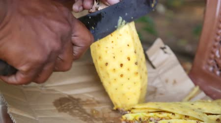 Ланка : Close up view of a local man cutting pineapple, a very popular fruit which grows all around Sri Lanka.