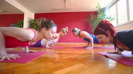 esneme : Group of attractive women doing yoga on rubber mats in hall Stok Video