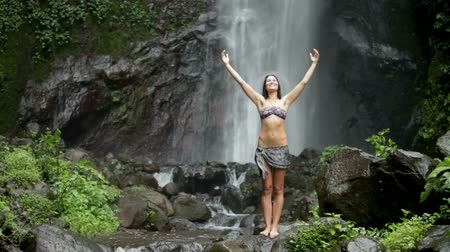 размышлять : Beautiful woman meditating close to waterfall in the tropics
