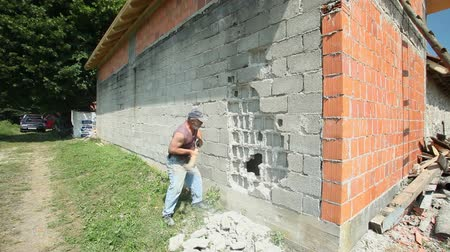 přetvořit : LIKA, CROATIA - JUNE 19, 2013: Worker knocking house wall down on June 19, 2013 in Lika, Croatia. The Serbian population fled and houses abandoned during the croatian war and now being rebuilt.