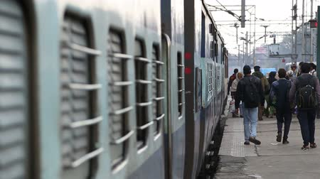 kolej : AMRITSAR, INDIA - 2 MARCH 2015: Train closeup, with people passing down the station.