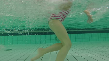 купаться : Little girl running underwater in swimming pool making bubbles Стоковые видеозаписи