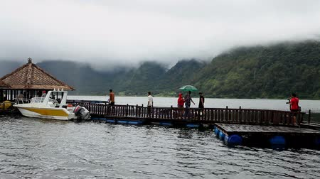 subsistence : LAKE BATUR, BALI - JANUARY 21: Tourist crossing jetty to restaurant on Lake Batur on January 21, 2012 in Bali, Indonesia. Inhabitants of the lake rely on tourism and fishing for their subsistence. Stock Footage