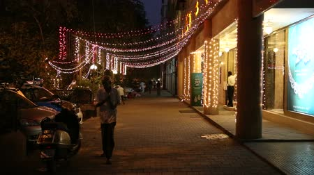 bombay : Shiny lights on the street of Mumbai, with people passing.