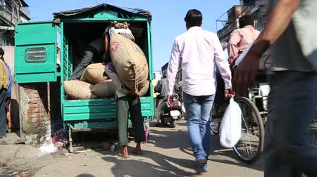 bazar : DELHI, INDIA - 4 MARCH 2015: Men waiting to load sacks in a truck, with people passing by them.