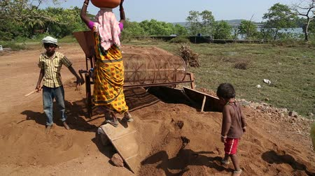 černoch : GOA, INDIA - 26 JANUARY 2015: Woman pouring soil in a processing machine, while children play. Dostupné videozáznamy