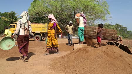 černoch : GOA, INDIA - 26 JANUARY 2015: Women taking children away from the field working site.