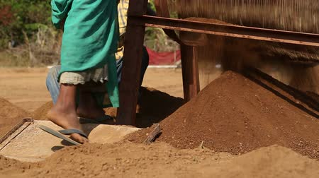 černoch : GOA, INDIA - 26 JANUARY 2015: Boy controlling machine that processes soil at field working site.