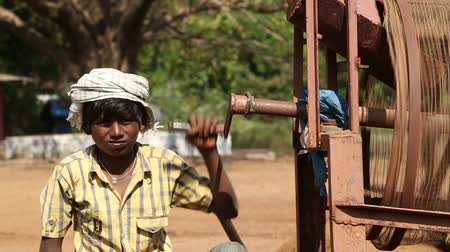 černoch : GOA, INDIA - 26 JANUARY 2015: Portrait of boy moving wheel of the soil processing machine.