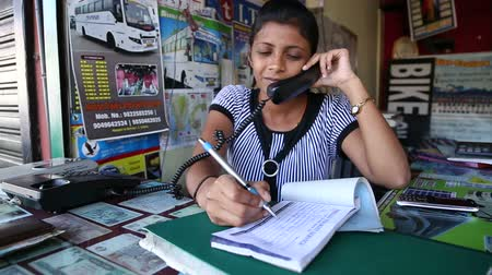 irodai dolgozó : GOA, INDIA - 27 JANUARY 2015: Portrait of Indian woman taking a reservation by the counter.