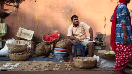 indian ethnicity : GOA, INDIA - 27 JANUARY 2015: Portrait of Indian man sitting at market stand while people are passing. Stock Footage