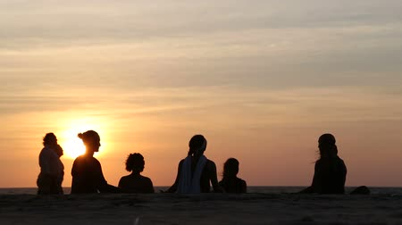 goa beach : Women meditating on the beach at sunset, with people passing.