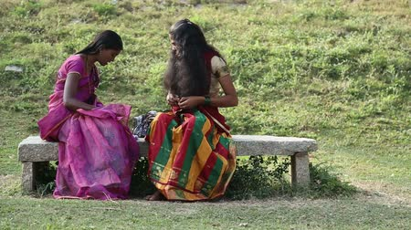 brown dress : HAMPI, INDIA - 28 JANUARY 2015: Two indian women sitting and combing their beautiful long dark hair.