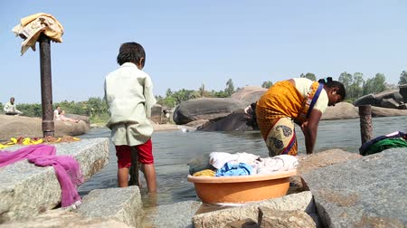 elefant : HAMPI, INDIA - 28 JANUARY 2015: Close view of woman and child washing clothes. Stock Footage