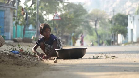 bída : HAMPI, INDIA - 28 JANUARY 2015: Little child picking up dried leaves in a pot on a street in Hampi. Dostupné videozáznamy