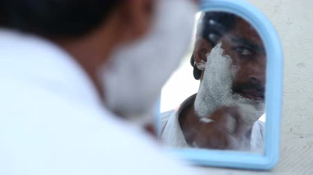 борода : HAMPI, INDIA - 28 JANUARY 2015: Portrait of man putting shaving cream on and looking himself at the mirror. Стоковые видеозаписи