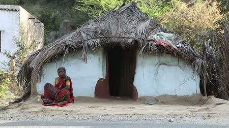 kulübe : HAMPI, INDIA - 28 JANUARY 2015: Woman sitting in front of traditional house in Hampi.